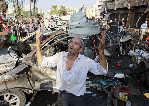 A man recites prayers amid the destruction after an explosion outside a mosque in the northern Lebanese city of Tripoli.