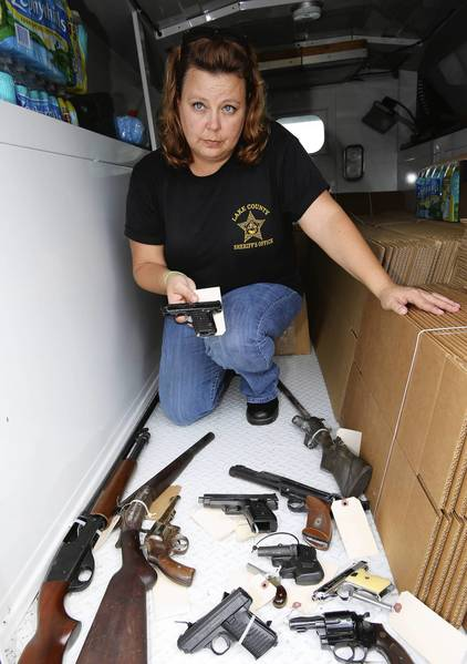 "Lake County evidence technician Kim Pratt poses with guns collected at Renningers including at least onestolen firearm . Officers collected firearms on Thursday, August 22, 2013, as part of the annual ""Kicks 4 Guns"" program. This is a joint effort of the Mount Dora Police Department and the Lake Sheriff's Office. The collection of the guns is anonymous and no questions are asked. In exchange for the gun, citizens are given gift cards, which are redeemable for shoes or other merchandise of their choosing at Walmart or Target. (Tom Benitez/Orlando Sentinel)"
