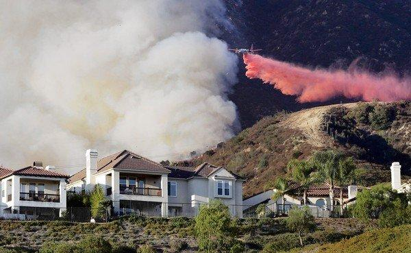 With more people choosing to live in rural areas closer to nature, the chances are greater than ever that someone you know will lose a house to a fire. Above, fire retardant is dropped on a burning hillside in Altadena in 2009.