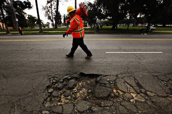 A worker places traffic cones to warn motorists of a large pothole; since 2005, Los Angeles has paid for normal upkeep and maintenance on streets of good quality, but has left a backlog of severely damaged roads largely untouched.