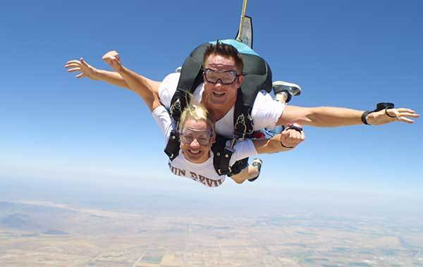 Christi Bruchok, shown here with her instructor, waited until after the fact to tell her parents she had gone sky diving in Arizona, one of many adventurous preludes to her recent 16,000-mile tandem bicycle trip with boyfriend Tauru Chaw.