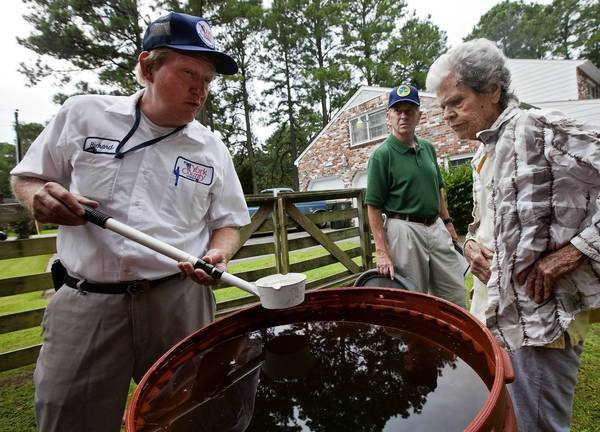 Tom Gallagher and Marilyn Eanes watch as Mosquito Control Technician Richard Laney (left) tests water for mosquito larvae at a home in Seaford on Friday.