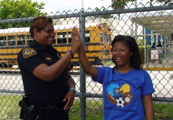 Miramar Police School Resource Officer Natasha Richardson high-fives Fairway Elementary school health technician Dyonte Robinson, for helping deliver baby Maybelle Colin Sainvilus in Miramar.
