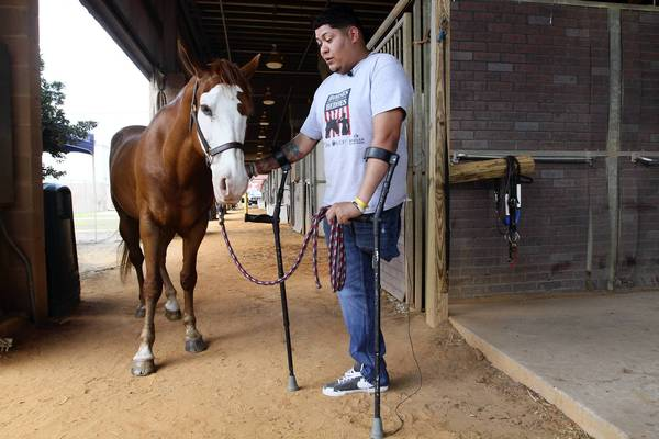 "Seemore and No ""Lito"" Santos, an Iraq war army veteran, is part of a group of veterans that participate in the Heavenly Hoofs program."