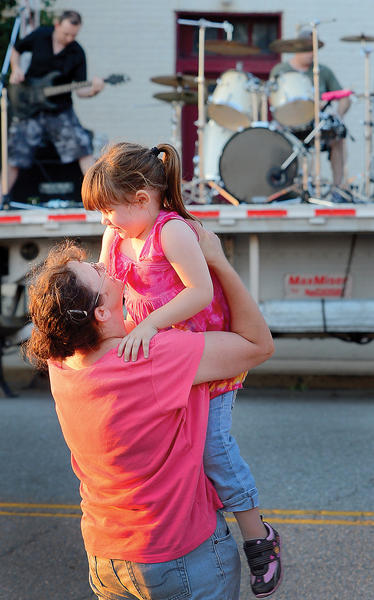 Cathy Starkey of Waynesboro, Pa., holds her three- year-old daughter, Elaina Spickler, in the air while listening to the sounds of the rock band Kubria Friday night at the inaugural River Rat Street Dance/Concert in Williamsport.