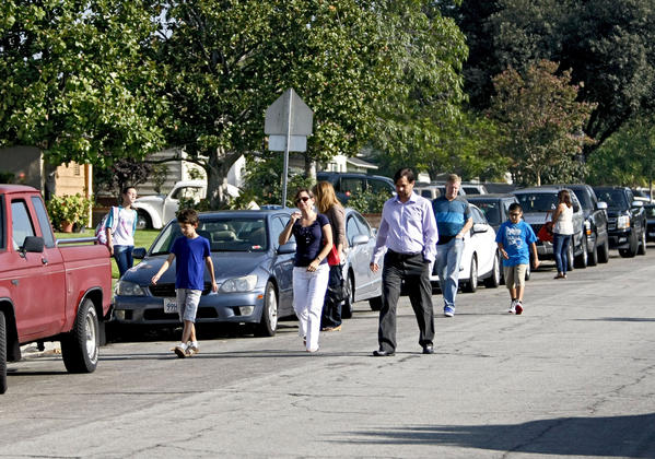 "Because there are no sidewalks and the public right of way is blocked with bushes and fences at many homes, parents and students walk along the road on the 1800 block of Screenland Drive as they head to orientation day for new students at Burbank Middle School in Burbank on Thursday, August 15, 2013. A woman walking her child to school commented that it was ""strange"" there were no sidewalks."