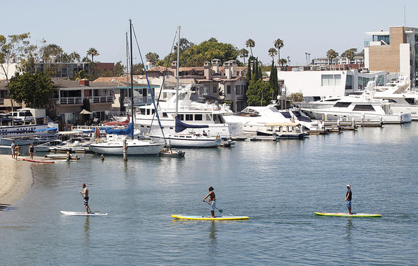 Paddle boarders cruise by a location where two yachts, one more than 100 feet long and the other more than 200 feet long, are to be anchored near west end of Lido Island in Newport Harbor.