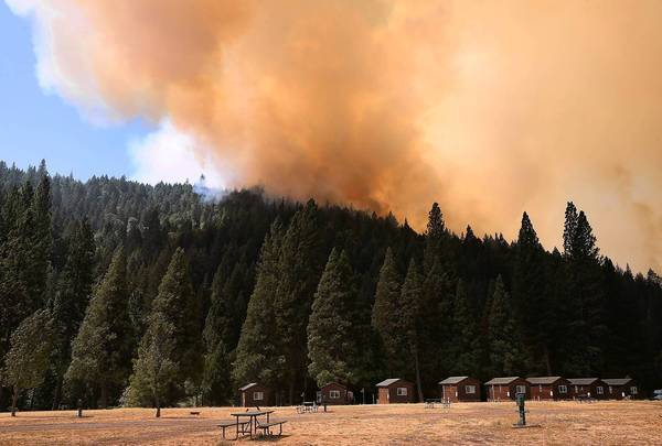 A plume of smoke rises above a ridge as the Rim fire approaches the Yosemite Lakes campground near Groveland, Calif., on Friday.