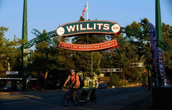 A bicycle rider makes his way on Main Street -- US Highway 101 -- through the town of Willits, in Mendocino County, where a four-lane freeway bypass is being built, requiring wetlands drainage.