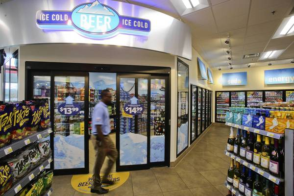Dave Masuku, an operations supervisor at the new RaceTrac store, at Forsyth and East Colonial Drive, spruces up at the store that features frozen yogurt service, a beer cave, and more high-end amenities, Thursday, August 22, 2013.