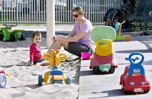 Jennifer Allen, 34 of Burbank, and her daughter Lucy, 22 months, are surrounded by toys left behind by others at Lincoln Park in Burbank. Children use the toys when they come to play in this fenced in area of the park.