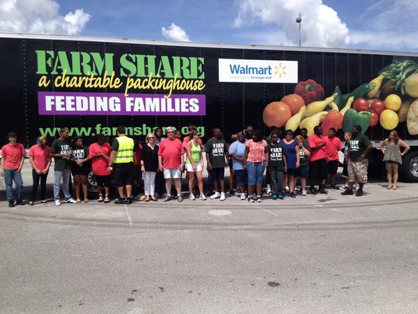 Volunteers who helped with a food distribution project in Sanford at the Seminole County Courthouse on Aug. 24, 2013 pose next to a trailer for Farm Share, the nonprofit that distributes donated food from Florida farmers to low-income families.