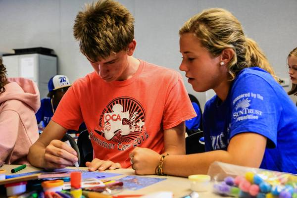 Caroline Hodson, 18, a student from Rollins College volunteers at Opportunity, Community, Ability Inc. doing arts and crafts with Giles Connolly, 16, in Orlando, FLA. on Saturday, August 24, 2013. More than 600 Rollins students will participate in community service projects at 30 local organizations as part of their fall orientation. (Joshua C. CrueyOrlando Sentinel)
