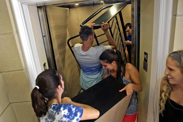 From left, Sarah Russell, John Pouchot, Chelsea Prescott, Preston Foote and Melissa Rizor attempt to fit inside an elevator with their belongings at Rappohannock River Hall on the campus of Christopher Newport University Saturday afternoon.