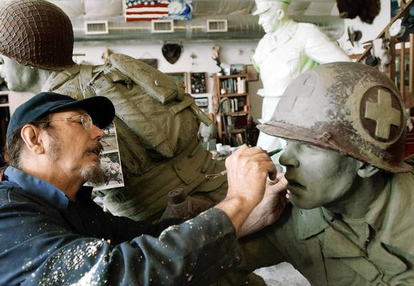 Kansas artist Jim Brothers works on a sculpture of a World War II medic for the National D-Day Memorial in Bedford, Va., in 2002.