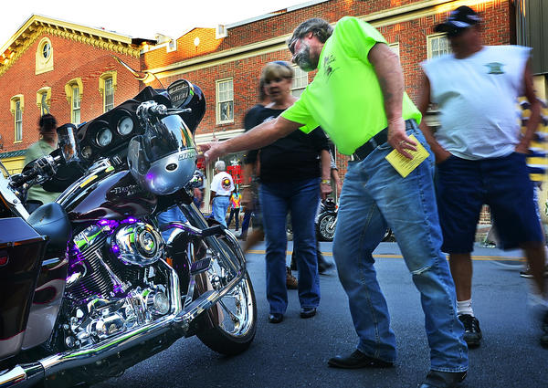 Alec Carroll of Harpers Ferry checks out a glowing Harley Davidson motorcycle Saturday evening at Martinsburg Bike Night.