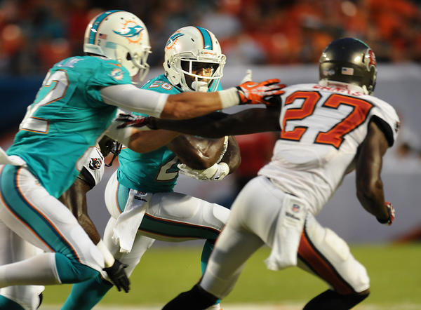 The Miami Dolphins host the Tampa Bay Bucaneers in pre-season action at Sun Life Stadium. Miami's Brian Hartline blocks Tampa's Johnthan Banks, cq, as Lamar Miller runs the ball. Robert Duyos, Sun Sentinel