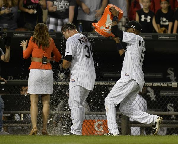 Alexei Ramirez douses Josh Phegley with ice water as he is interviewed by a reporter.