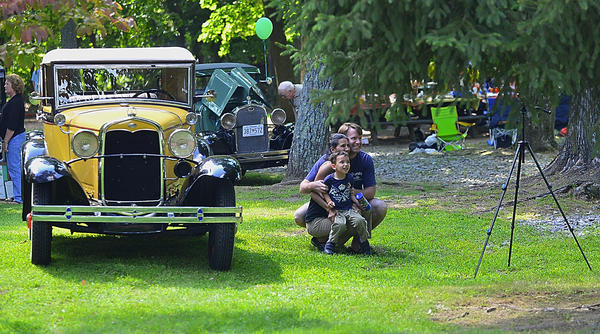 Jim and Elisa Hamilton and their 3-year-old son Francisco drove from Baltimore to enjoy Everybody's Day Sunday at Pen Mar County Park near Cascade. They are posing for a family picture beside an antique Ford.