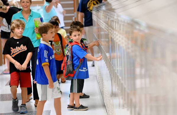 Cole Benson-Williams, 5, (right), looks at the new lockers inside Stoneleigh Elementary School. He is entering kindergarten and will not get a locker until first grade. The school will reopen after massive rennovations and an expansion. Students and parents came to see the school before the start of the school year on Monday.