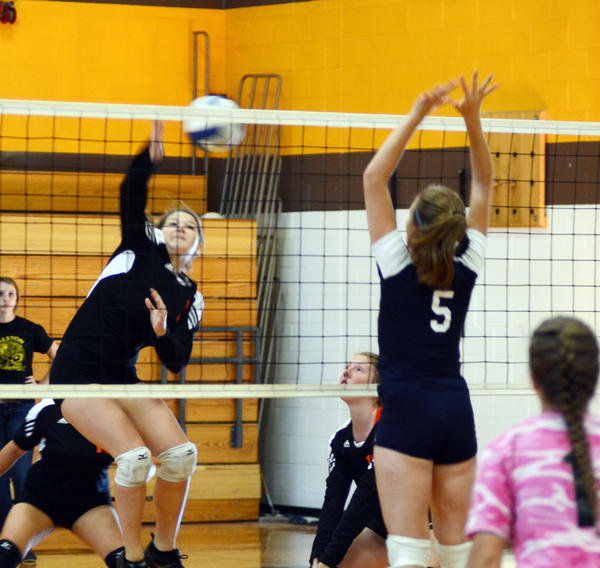 Harbor Springs Sydney Elkins (left) blasts a shot past Bay City All Saints Paige Judd (5) during the Pellston Volleyball Invitational Saturday at the Pellston High School gym.