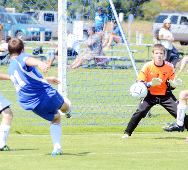 Burt Lake NMCA goaltender, Christian Vinz (right) attempts to stop Saginaw Nouvel Catholics Nathan Garpiel (left) shot on goal during the NMCA Soccer Invitational at The Click Road Soccer Complex Saturday.