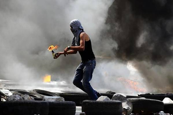 Palestinian protester gets ready to throw a Molotov cocktail during small clashes with Israeli forces following the funerals at Qalandiya Refugee Camp near Ramallah.