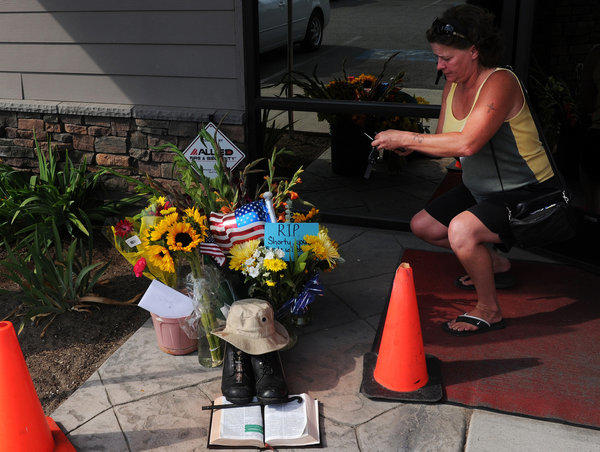 Lill Duncan takes a photo of a memorial for Delbert Belton, an 88-year-old World War II veteran who was beaten to death, in Spokane, Wash. Police arrested a second suspect on Monday.
