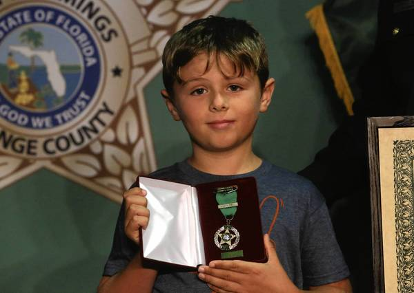 Sheriff Jerry Demings honored 9-year-old Ethan Temmen, a visitor from England, with saving a girl from drowning inside a hotel pool. He holds his citation medal.