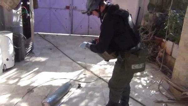 An image from amateur video purports to show a U.N. inspector measuring and photographing a canister in the Damascus suburb of Muadhamiya in Syria.