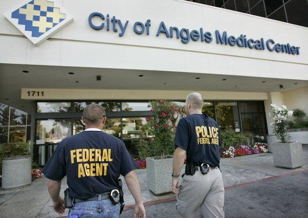 Law enforcement personnel from multiple local and federal agencies enter the City of Angels Medical Center in Los Angeles in 2008 as search warrants were served on it and two other hospitals.