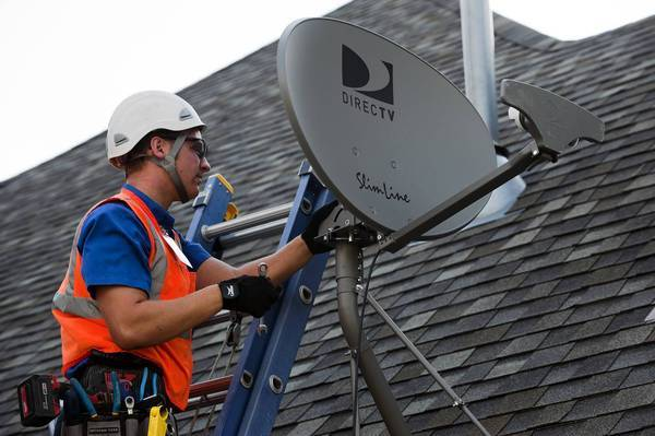 Jordan Schlupe, a DirecTV employee, installs a satellite dish in Bixby, Okla., in June. The firm asks potential customers for their Social Security numbers.