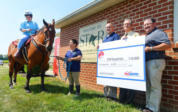 PetSmart presents a check for $10,000 to Star Community on Monday afternoon. From left are Sandy Snyder, a Star Community resident and rider; Myra Holler, a Star Equestrian volunteer; Charlie Keller, operations manager for the PetSmart distribution center in Hagerstown; Dallas Hopkins, Stars executive director; and Todd Appleby, general manager of the PetSmart distribution center in Hagerstown.
