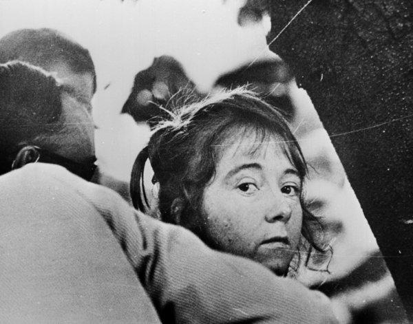 "Lynette ""Squeaky"" Fromme, an acolyte of Charles Manson, being led away after her failed attempt in 1975 to kill President Ford."