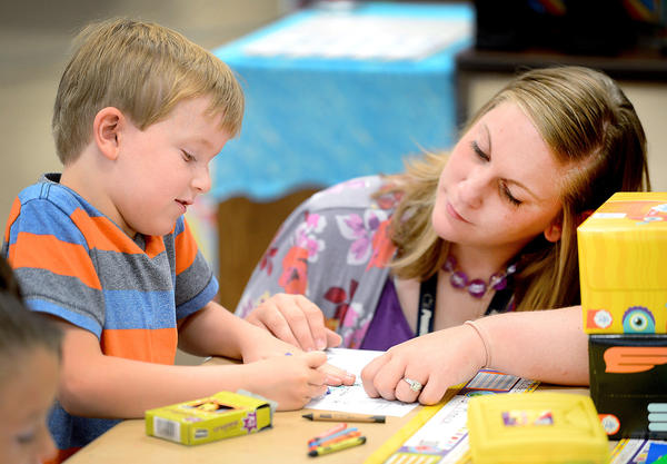 Mowrey Elementary School first-grade teacher Tiffany Corl, right, helps J. Minnick break in his new crayons Monday morning on the first day of school in Franklin County, Pa.