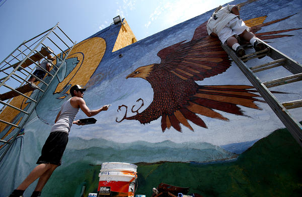 Levi Ponce, center, is assistaed by fellow mural artists as he works towards completing his latest and likely last mural on Mural Mile along Van Nuys Blvd. in Pacoima.