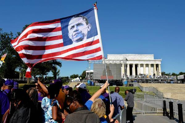 A woman holds a flag depicting President Obama as she participates in Saturday's March on Washington commemoration. Obama, who did not join the event, will deliver an address Wednesday marking the 50th anniversary of the march.