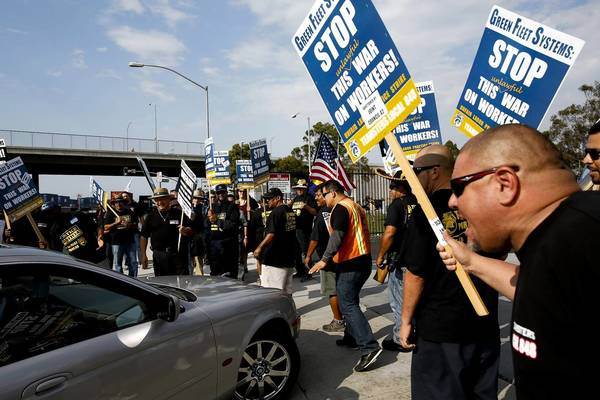 Truck drivers on strike and their supporters demonstrate outside Green Fleet Systems' facility in Carson.