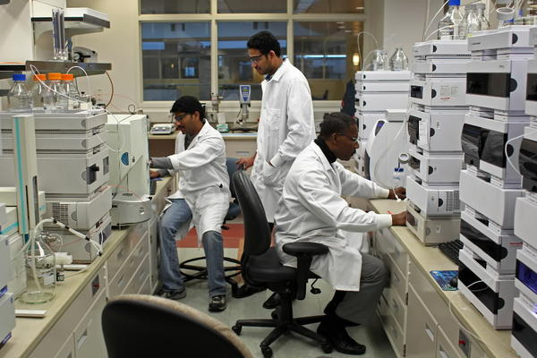 Research chemists Rama Gollapalli, (cq) from left, and Srikanth Penumetsa, (cq) analyze molecular ions in pharmaceutical products while Magnus Obiobasi, a scientist, reads incoming data at Akorn, a pharmaceutical company, in their Skokie lab on Thursday.