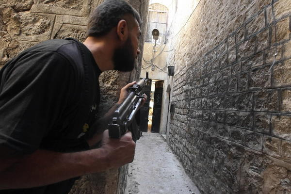 A Free Syrian Army fighter holds his weapons as he peeks at an alleyway in al-Jdeideh neighborhood in the old city of Aleppo.