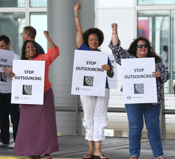 United Airlines workers hold signs rejecting the outsourcing of jobs outside of Terminal 1 at Chicago O'Hare International Airport.