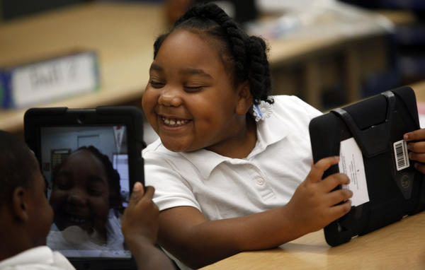 Tiannah Dizadare gives a big smile to schoolmate Avery Sheppard as they explore their new LAUSD-provided iPads at Broadacres Elementary School.