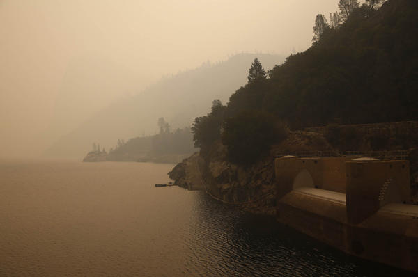 The Hetch Hetchy reservoir and spillway gates on the O'Shaughnessy Dam glow yellow under a fog of dense smoke from the nearby Rim fire.