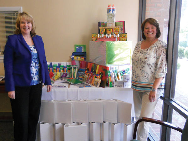 Edward Jones financial adviser Amy Forman, left, and branch office administratorKelli Boyer display the school supplies donated by community members for Salem Avenue Elementary School.