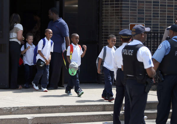 Officials move children out of Mollison Elementary School in Chicago on Tuesday after a power outage.