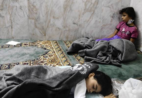 Girls who survived from what activists say is a gas attack rest inside a mosque in the Duma neighborhood of Damascus