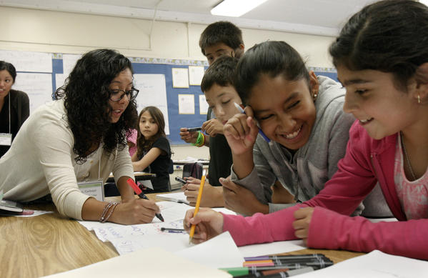 A new law will extend the length of graduate teacher training programs to two years. Here, Angie Carbajal, left, a trainee in the Urban Teacher Residency preparation program, instructs students at Gage Middle School in Huntington Park.
