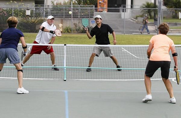 Nancy Bendel, left, and her partner Diane Farrell play a game of pickleball against Jim Michael, left, and Dewayne Ichiriu at Worthy Park in Huntington Beach.