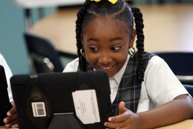 Beautiful Morris smiles as she works on her new iPad, provided by the Los Angeles Unified School District.