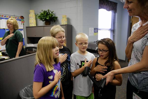 Nine-year-olds Nicole Augustyniak, Jacob Keith, Evan Kruse and Olivia Muci, from left, recite the Pledge of Allegiance at Evergreen Elementary School in DuPage County's Benjamin School District 25, one of 71 Illinois districts that held a shortened first day despite a new state law intended to prevent that.